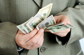 Businessman counts money in hands. — Stock Photo