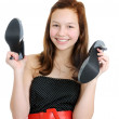 Portrait of a smiling teenage girl holding high heel shoes isolated on the white background - Stock Photo