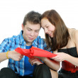Smiling teenage girl and boy cutting valentine heart out of red paper with scissors over white background — Stock Photo