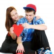 Smiling teenage girl and boy holding a valentine cut out from red paper with scissors over white background — Stock Photo #18625899