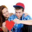 Smiling teenage girl and boy holding a valentine cut out from red paper with scissors over white background — Stock Photo #18625909
