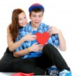 Smiling teenage girl and boy holding a valentine cut out from re — Stock Photo