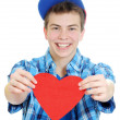 Smiling teenage boy holding valentine heart cut out from red paper over white background — Stock Photo #18625953