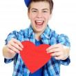 Smiling teenage boy holding valentine heart cut out from red paper over white background — Stock Photo