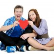 Smiling teenage girl and boy holding a valentine cut out from red paper with scissors over white background — Stock Photo