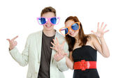 Young happy smiling couple wearing a big colored glasses having fun on white background — Stock Photo