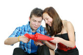 Smiling teenage girl and boy cutting valentine heart out of red paper with scissors over white background — Foto Stock