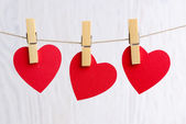 Red hearts hanging on wooden background — Stock Photo