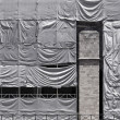 Photo: Building covered with wrinkled tarpaulin canvas