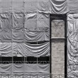 Building covered with wrinkled tarpaulin canvas — 图库照片