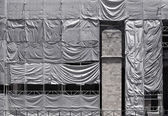 Building covered with wrinkled tarpaulin canvas — Stok fotoğraf