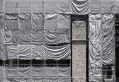 Byggnad täckt med skrynkliga presenning duk — Stockfoto