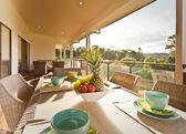 Dinner table on a covered verandah — Stock Photo