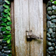 Stock Photo: Old wooden door in stone wall