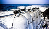 Air tanks and breathing apparatus on a boat — Stock Photo