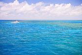 Far away luxurious yacht sailing across the ocean — Стоковое фото