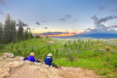 Senior hikers are watching sunset in the firled of wild flowers and ocean. — Stock Photo