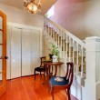 Hallway with white staircase and hardwood floor. - Photo