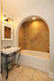 Tub with arch and stone tiles and sink bathroom design. — Stock Photo