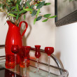 Stock Photo: Cart with red glasses and vase with olives. House details.