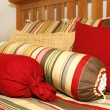 Stock Photo: Bed and pillows in red, yellow and green stripes.