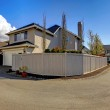 Beige house from backyard with garage and fence near road. — Stock Photo