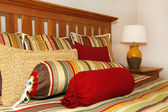 Bed details in red, yellow and green with wood head board. — Stock Photo