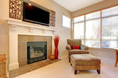 Fireplace with large TV above, elegant chair with windows. — Stock Photo