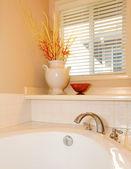 Witte tub met vaas en venster hoek met beige muur. — Stockfoto