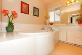 Bathroom with large round white tub and cabinets with double sink. — Stock Photo