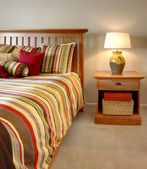 Wood bed and nightstand with stripes in red, yellow and green. — Stok fotoğraf