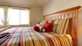 Cama grande con ropa de cama hermosa en raya roja, amarilla y verde. — Foto de Stock
