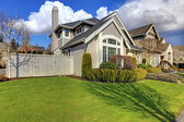 Classic American house with fence and green grass during spring. — Stock Photo
