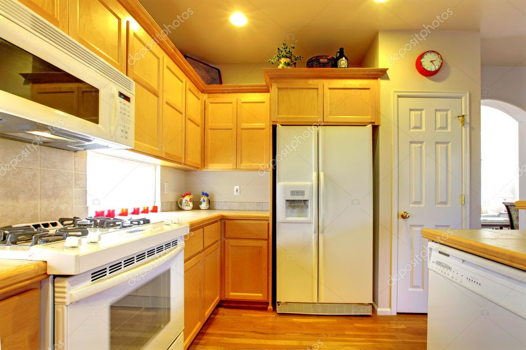 Kitchen with yellow wood cabinets and white appliances ? Stock