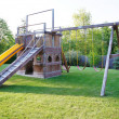 Kids playground in fenced back yard of house. — Stock Photo