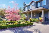 Grey large luxury house with spring blooming trees. — Stock Photo