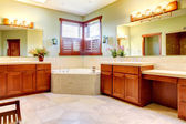 Large bathroom with double wood cabinets and corner tub. — Stock Photo