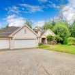 Large beautiful beige and grey house garage exterior during summer. - Stock Photo