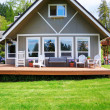 Modern American farm cottage house exterior with deck. — Stock Photo
