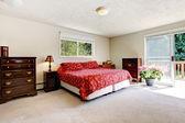 Bedroom with red bed, open balcony door and beige walls. — Stock Photo