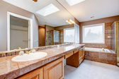 Large luxury bathroom with red granite countertops and tub. — Стоковое фото