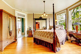 Large historical Inn room interior - bedroom with antique bed. — Stock Photo
