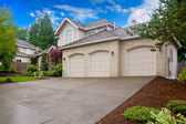 Large beige house with three car garage and large driveway. — Stock Photo
