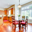 Dining room and kitchen with red cherry wood and large window. — Stock Photo #13894615
