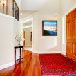 Large home luxury entrance with red rug and wood door. - Stock Photo
