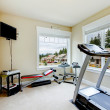 Home gym with equipment, weights and TV. — Stock Photo