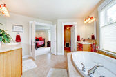 Large bathroom with white tub and open door to bedroom. — Stock Photo