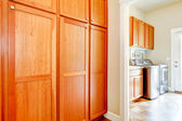 Laundry room with wood storage cabinets. — Stock Photo