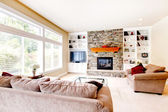 Large bright living room with fireplace and beige sofas. — Stock Photo