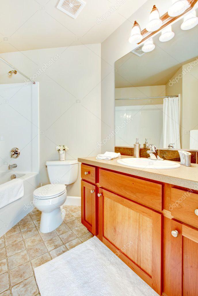 Banheiro com banheira branca, vaso sanitário e pia e armários de madeira — Fo -> Armario Banheiro Vaso Sanitario